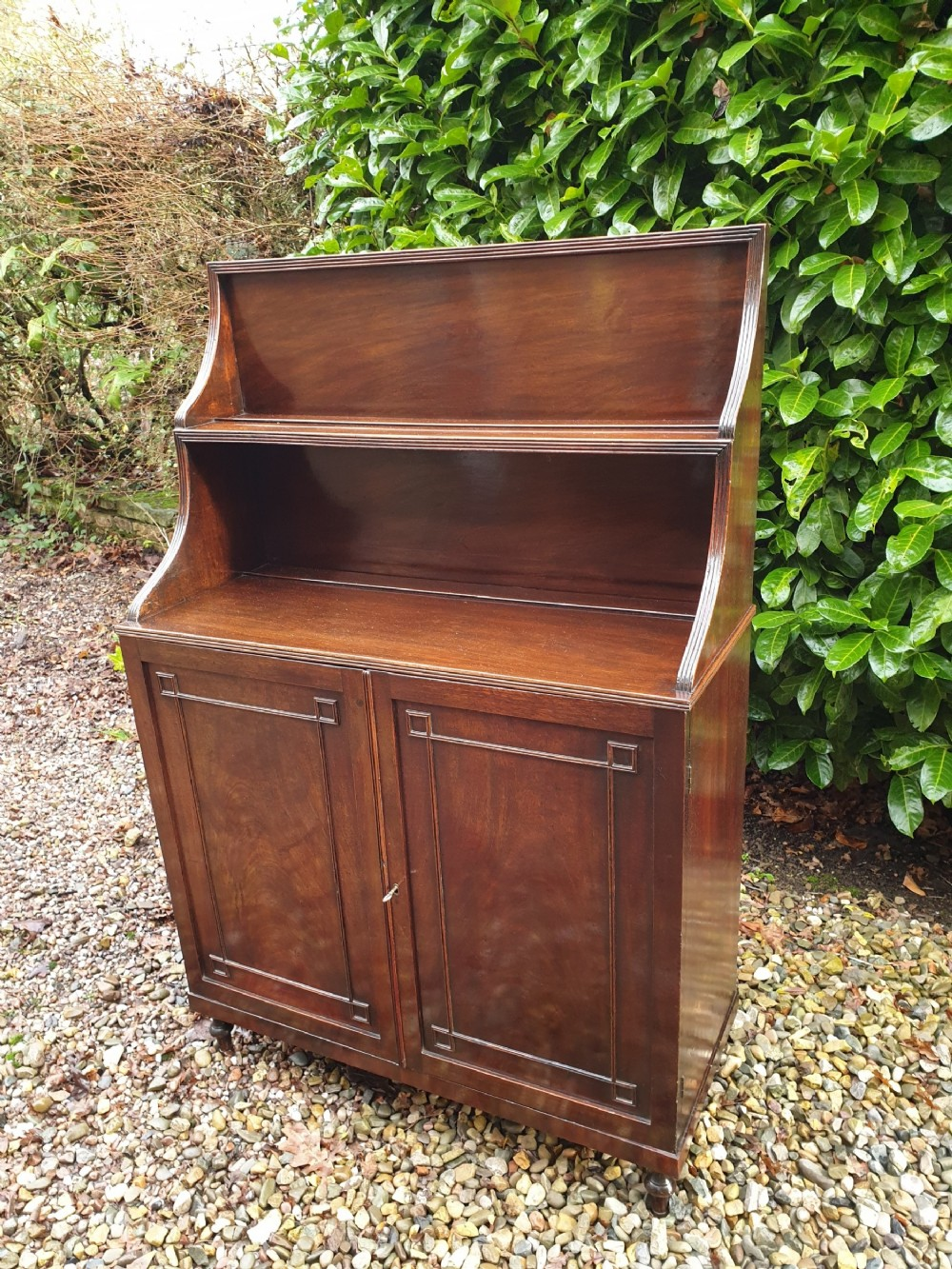 a georgian elegant mahogany open bookcase with a cupboard base